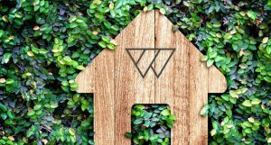 A Wondrwall branded wooden house model on a wall of foliage.